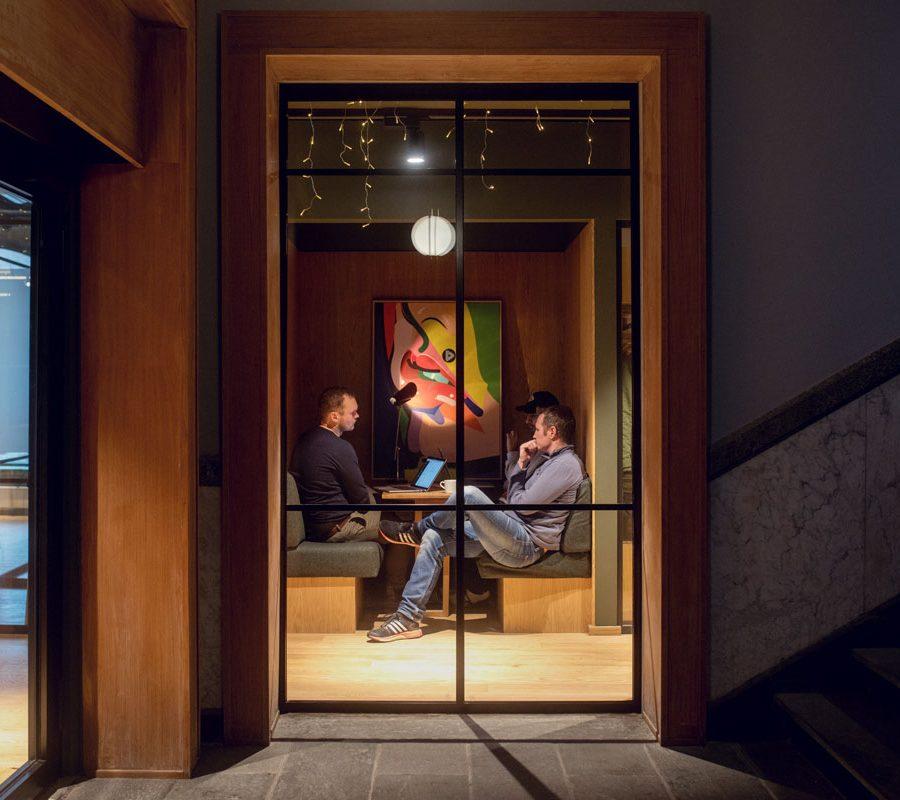 Foto av kontoret til Dekode, sette utenfra og inn glassvegg der tre personer sitter rundt en pc og jobber.
