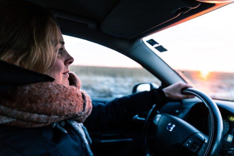 Dame som kjører bil med stort skjerf rundt halsen. Bildet hentet fra Kongelig Norsk Automobilklub