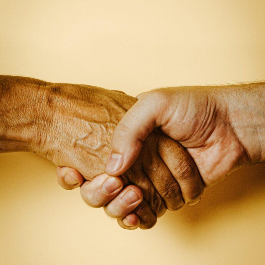 Foto av to som tar hverandre i hendene