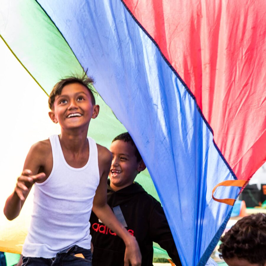 Bilde av en glad, ung gutt i noe som kan ligne på en flyktningleir.