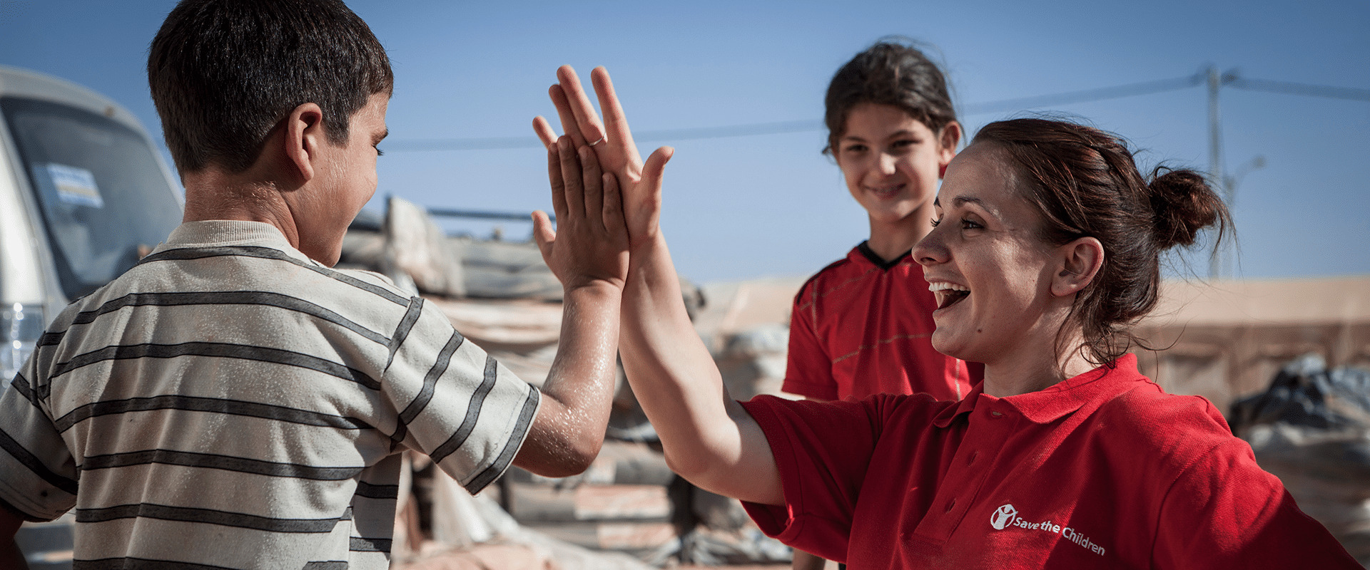 Image of a Save the Children-employee hig-fiving a young boy.