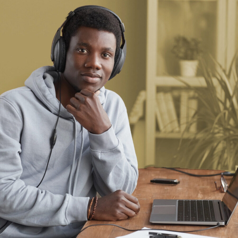 Image of a student with headphones around his neck, in front of his laptop