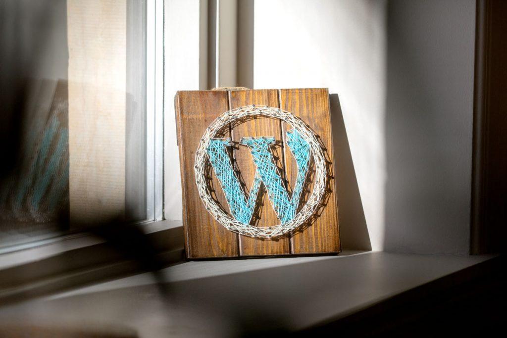 Foto av en treplate som står i vinduskarmen, med WordPress logoen laget i tråder.