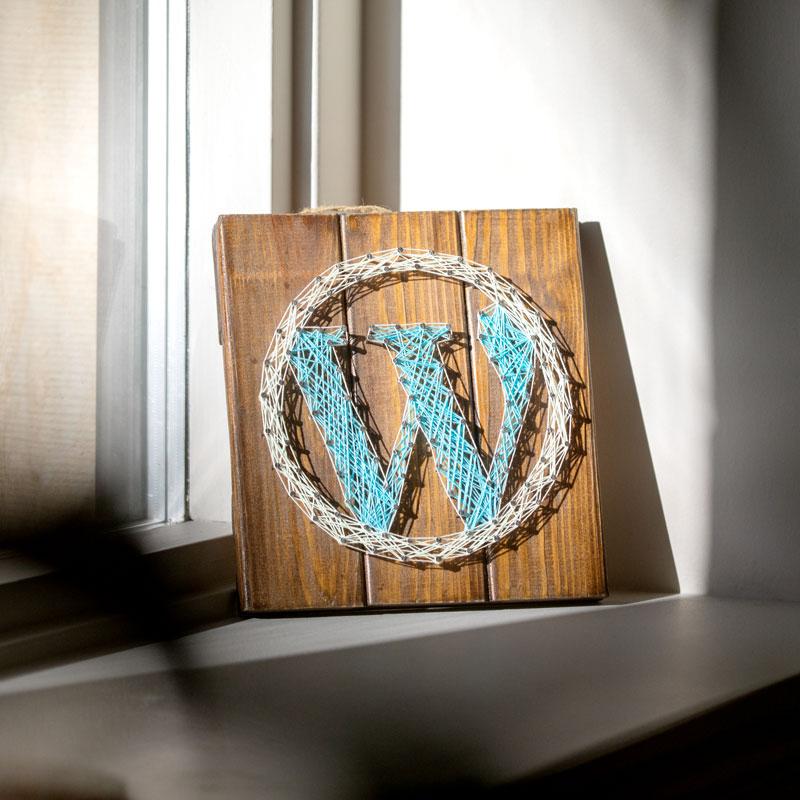 Treplate med WordPress logoen brodert står i vinduskarmen hos Dekode.