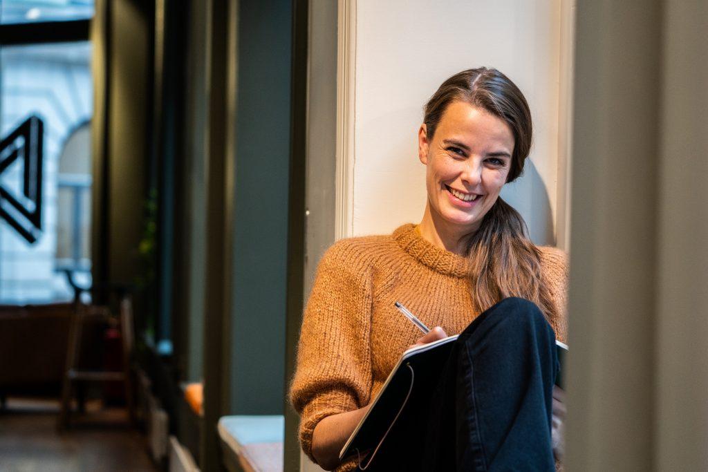 Cecile sitter i vinduskarmen og tegner i notatbok. Cecile er digital designer i Dekode. Foto: Henning Hovland