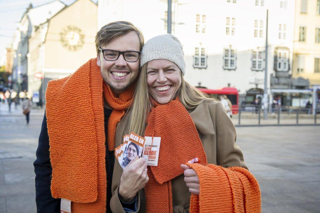 Kristian Badendyck Fjeldstad og en kvinne fra Kirkens Bymsjon står på Karl Johan med oransje bymisjon-skjerf på seg og til å dele ut.