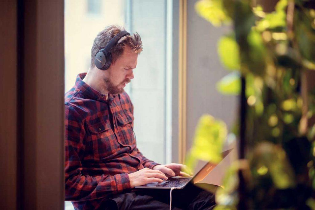 Foto av daglig leder i Dekode, Magne Ilsaas som jobber på en mac med headset i vinduskarmen på kontoret