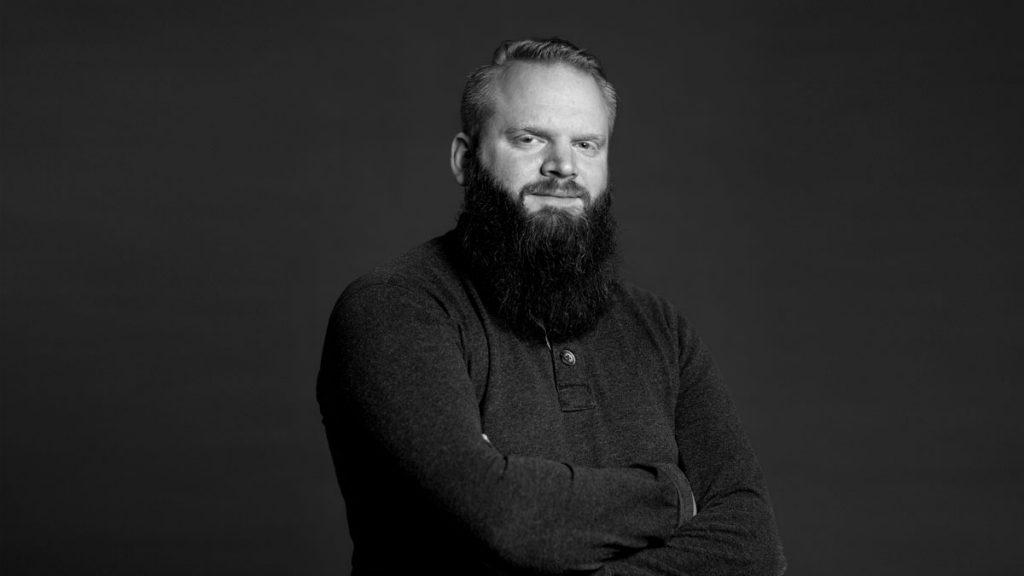 Marius Jensen, seniorutvikler i Dekode, poserer mot mørk bakgrunn.