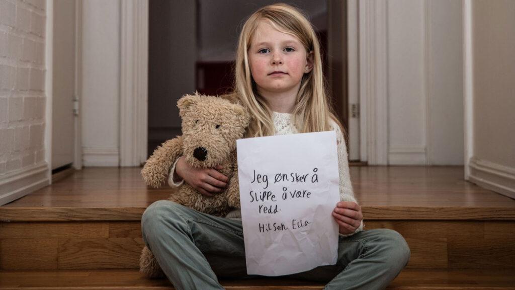Jente sitter med bamse og lapp - Jeg ønsker å slippe å være redd.