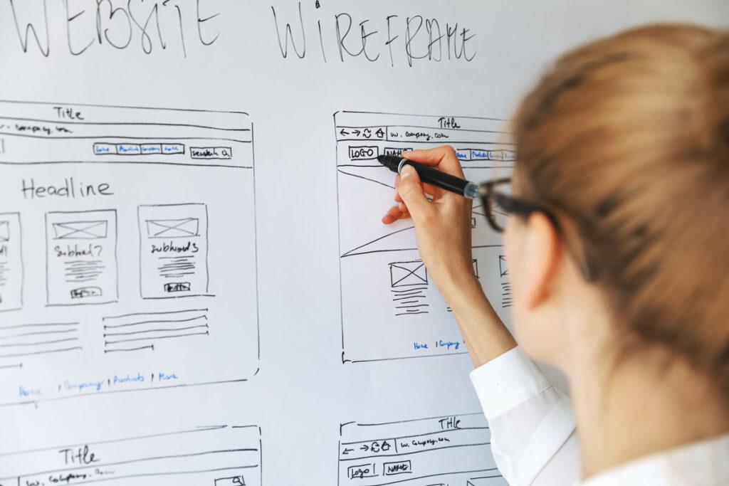 Foto av dame som designer en wireframe på et whiteboard
