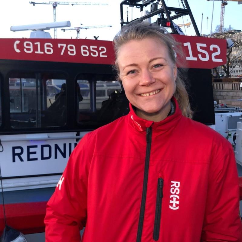 Portrettfoto av Eirin Heddeland, redaktør for Ett RS. Hun har på seg rød jakke og står foran en redningsskjøyte.