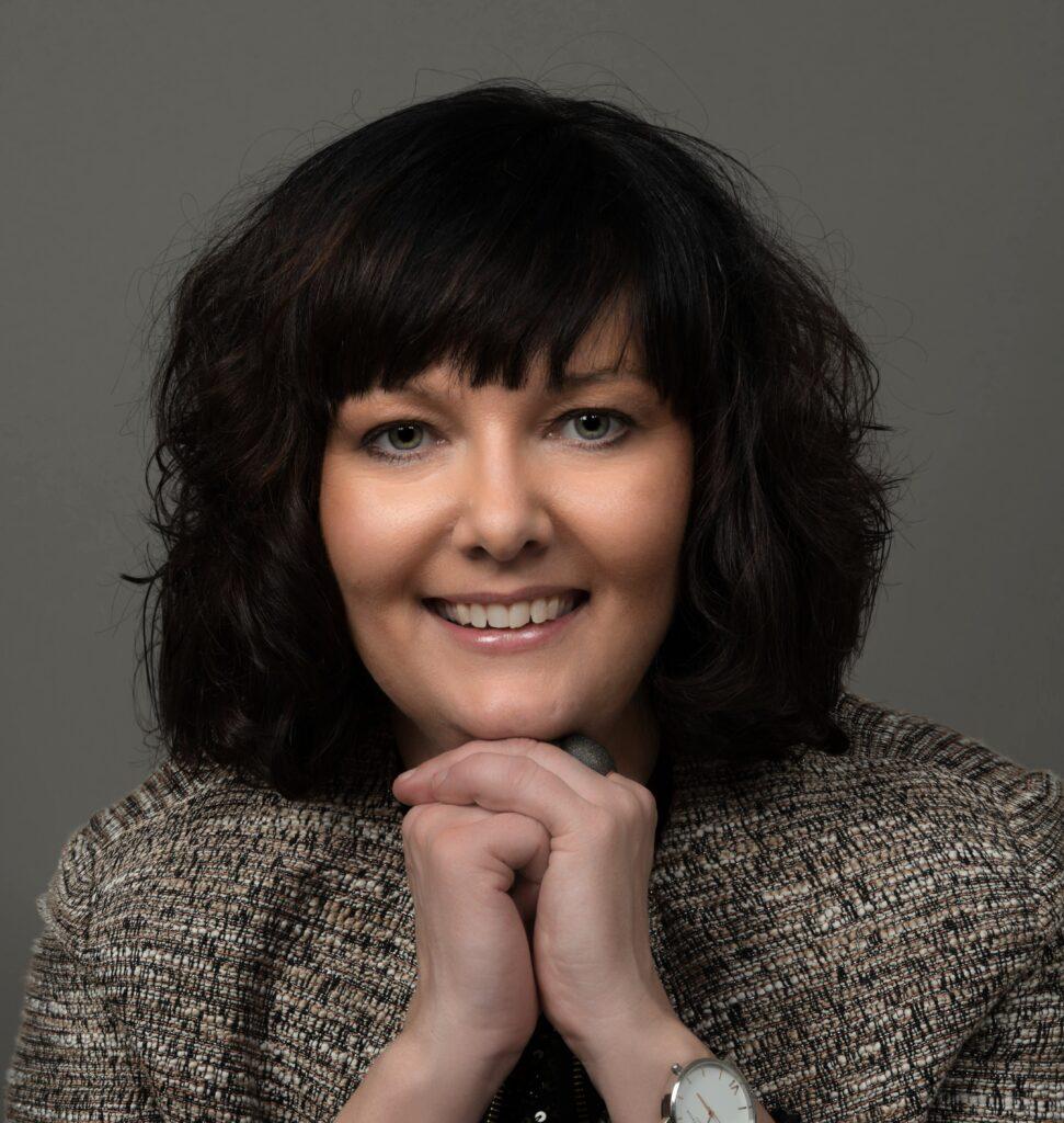 Portrettfoto av Malin Rygg, Tilsynsleder i Tilsyn for universell utforming av IKT, med grå bakgrunn.
