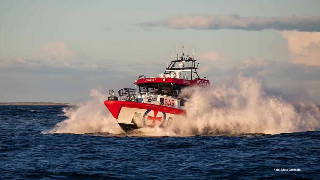 Foto av en redningsbåt med Redningsselskapets logo på som kjører fort på havet, med sjøsprøyt rundt.