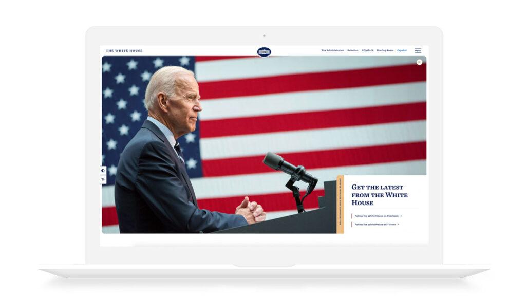 Bilde av en mac-skjerm med forsiden til det hvite hus sine nettsider oppe. Forsiden viser et stort bilde av President Joe Biden med det amerikanske flagget i bakgrunn.