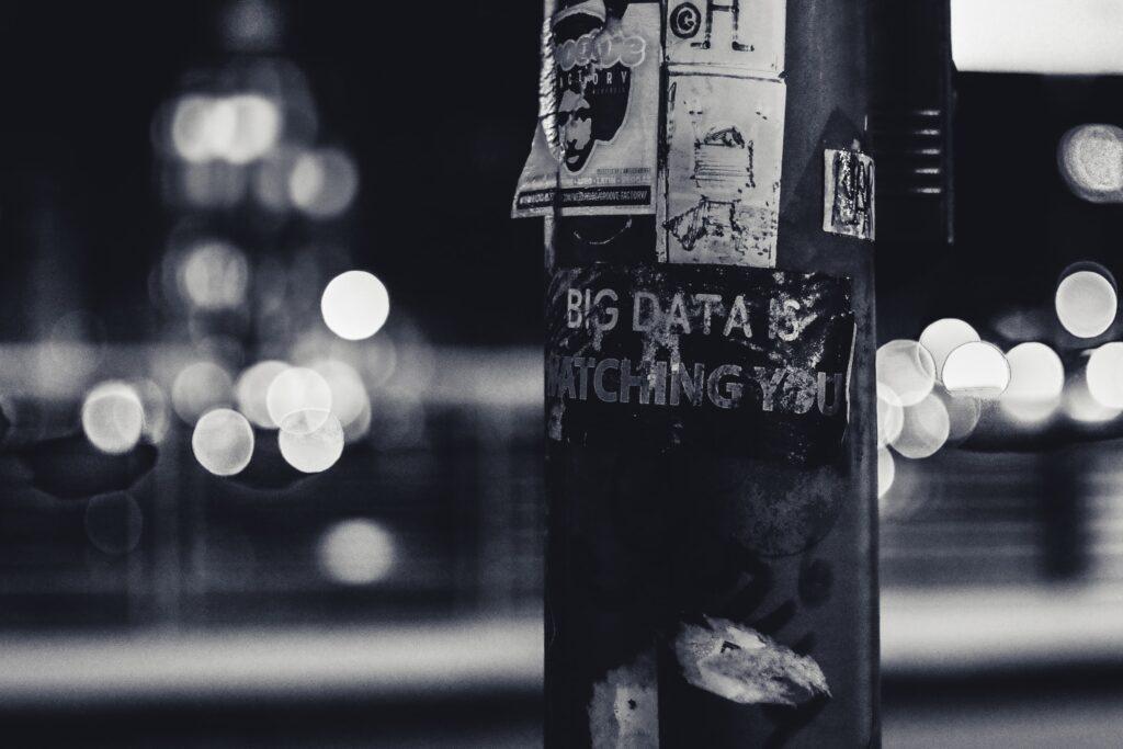 Sort/hvitt foto av en lyktestolpe med diverse plakater på, inkludert ordet Big data som symboliserer digitalisering.