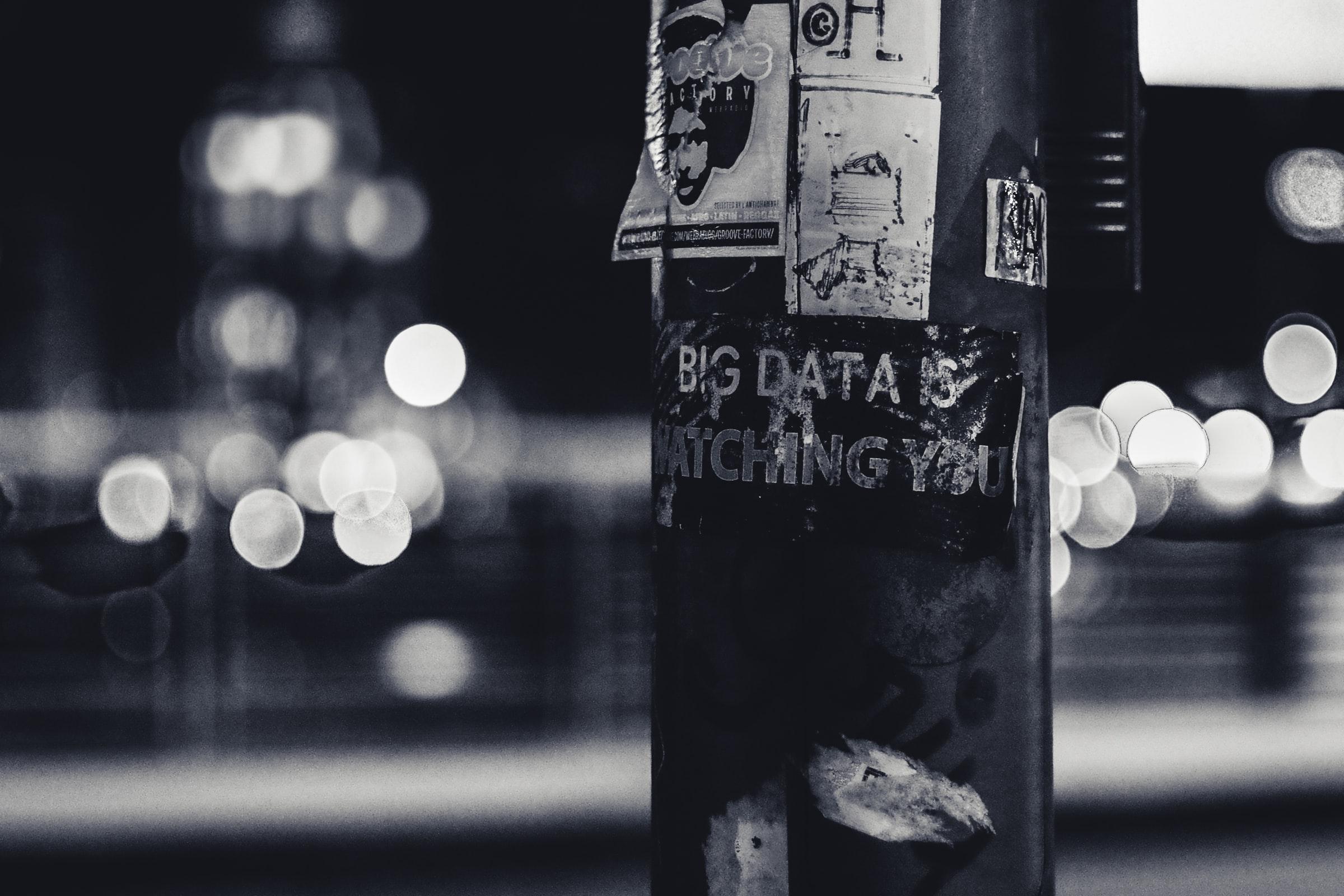 Sort/hvitt foto av en lyktestolpe med diverse plakater på, inkludert ordet Big data.