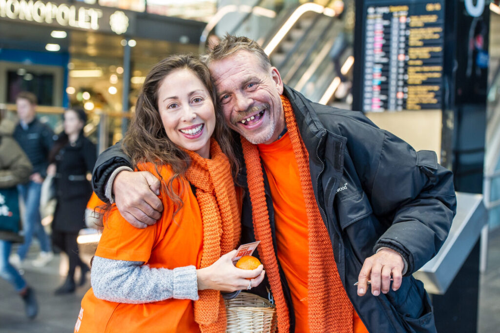 To smilende personer med oransje skjerf
